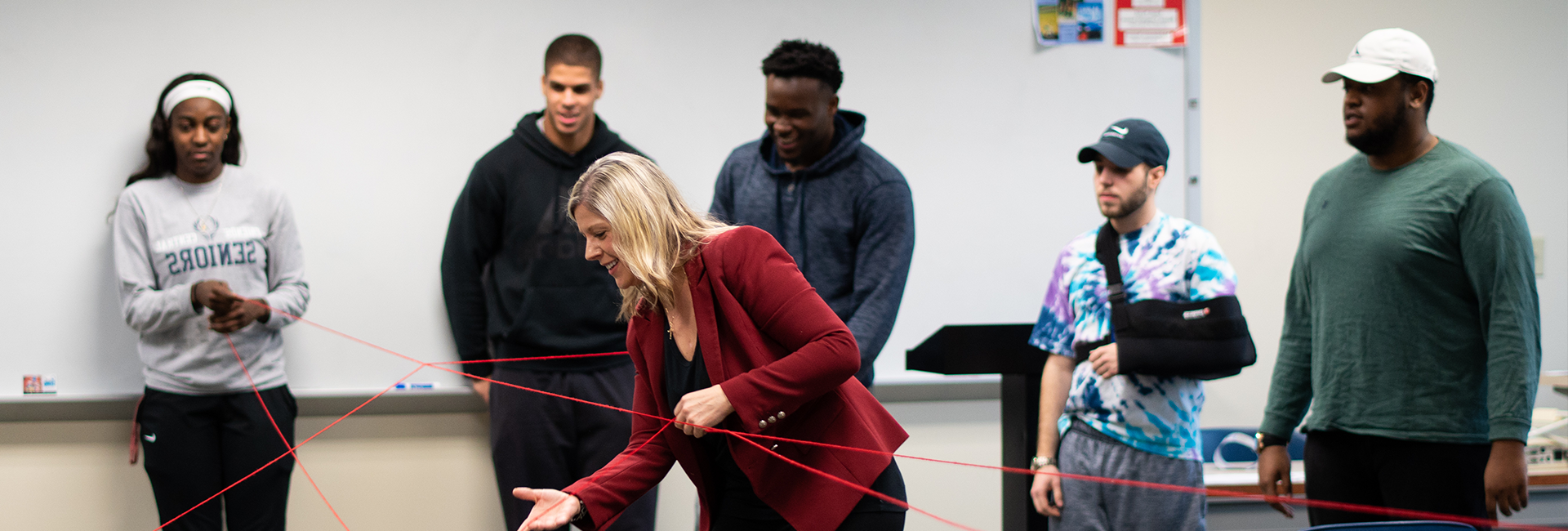 Professor working with string to give a management lesson with 5 students watching her