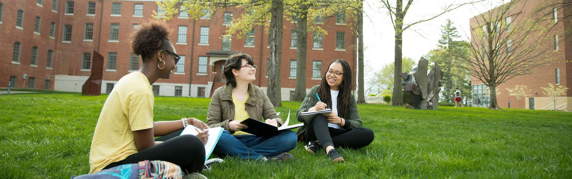 three students sitting on a lawn talking to eachother
