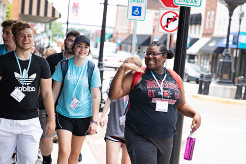 group of new SEMO students walking along a sidewalk in downtown Cape Girardeau