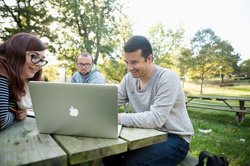 three students sitting at a picnic table outdoors gathered around an open Macbook laptop