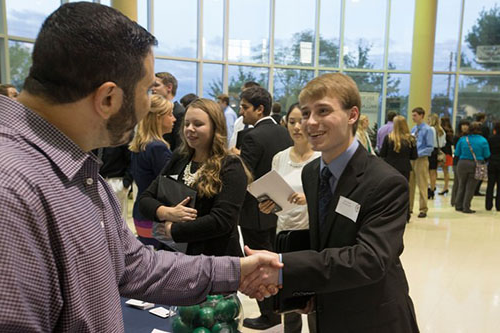 student shaking hand with employer