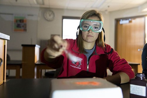 student wearing goggles measuring out item on scale