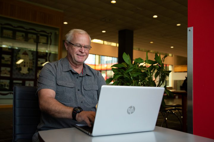 non-traditional student, older man sitting at a table with his laptop