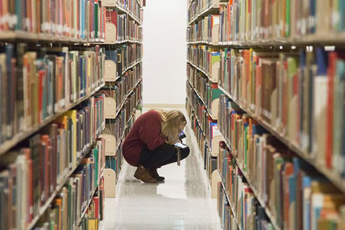 student browsing library shelf