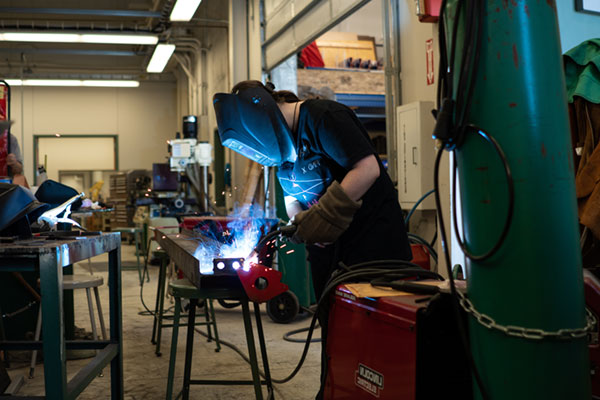 student in a workshop wearing a welding mask working with a welder