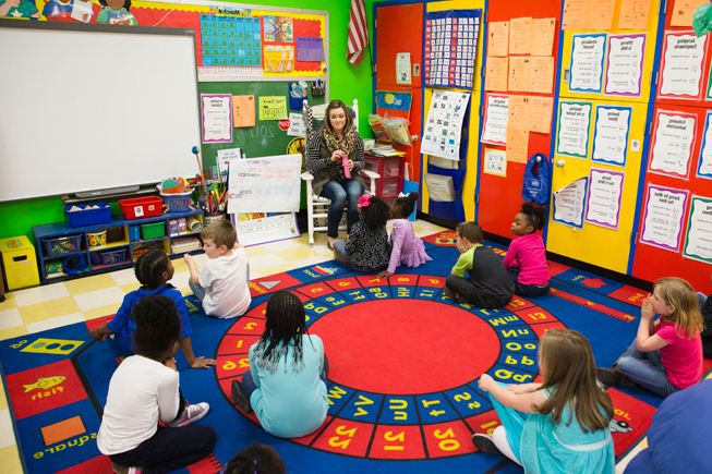 student teacher sitting with group of children in a brightly colored classroom