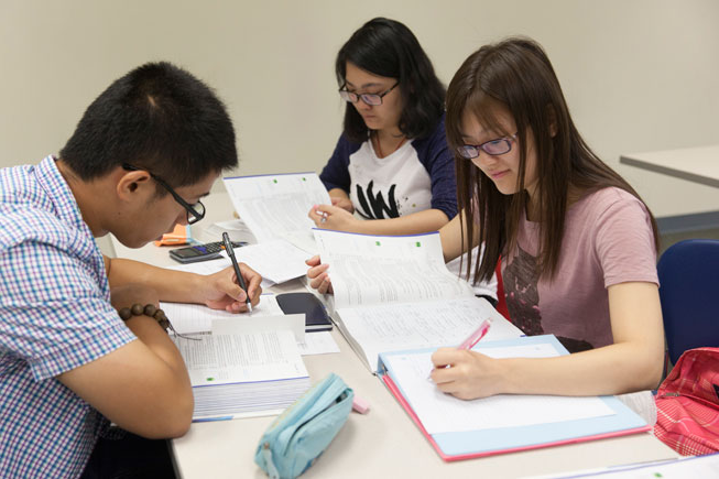 students gathered together at a work table with papers and books spread out in front of them