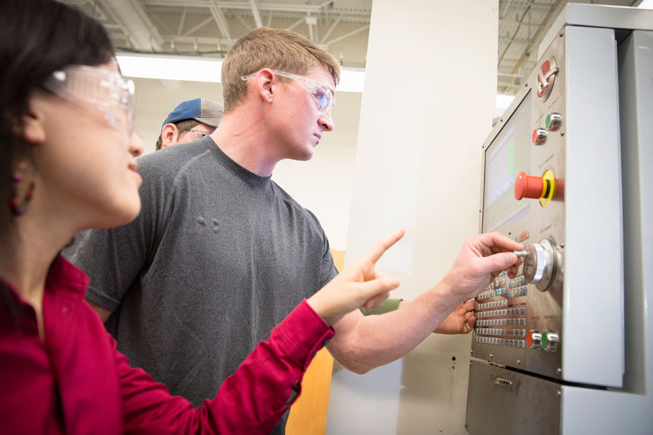 Student and instructor wearing safety glasses standing in front of a piece of equipment. the student is making adjustments to a knob on the machine while the instructor provides direction