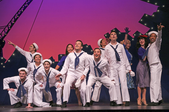 students on stage in sailor outfits posing in front of a stylized city sunset backdrop and pointing out over the audience