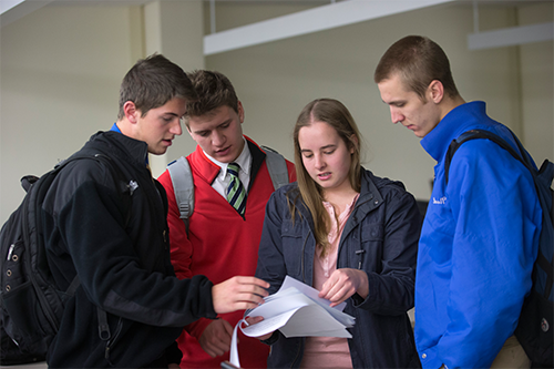 four students working together and all looking at a piece of paper