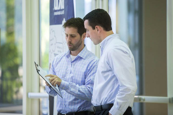 two men standing side by side going over information on a clipboard