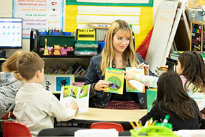student teacher with a class of small children choosing books to read