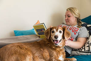 student with her dog in her dorm room