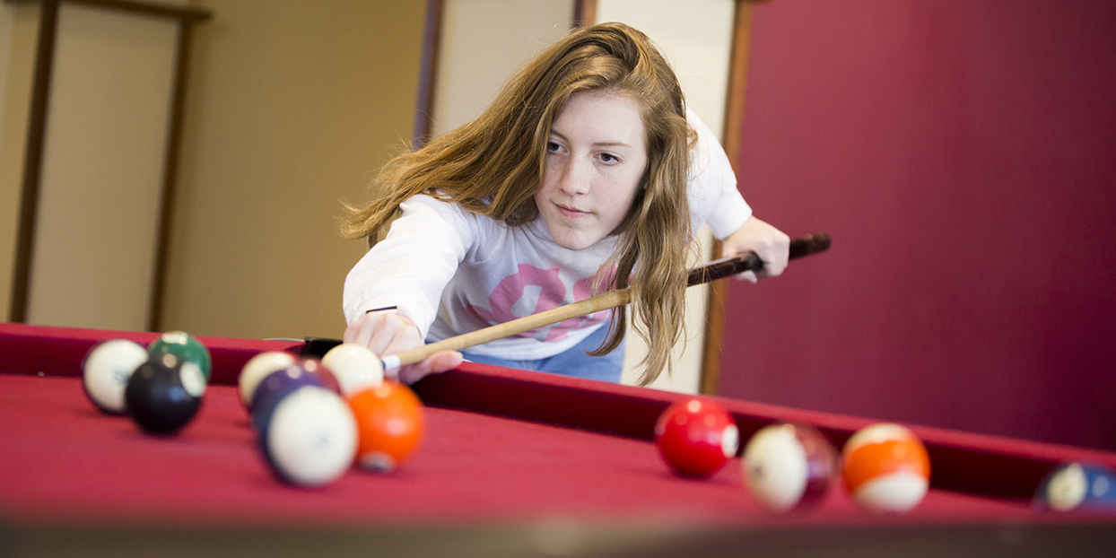girl playing pool bent over table lining up shot
