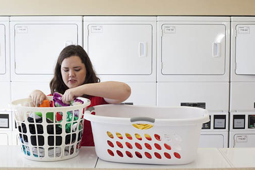 student in laundry room with baskets of clothes
