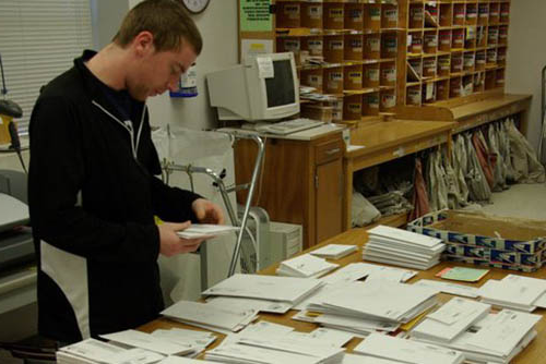 worker with table full of mail in mail room