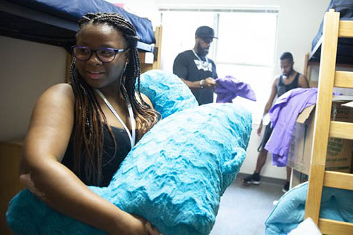 student in her dorm room holding a pillow