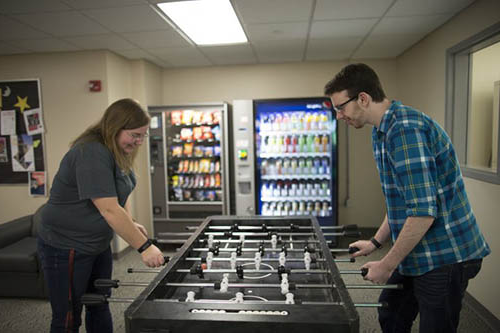 students at game table with vending machines in background
