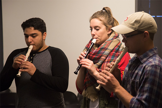 Three student teachers playing the recorder